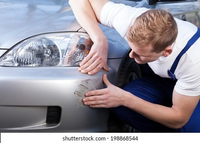 A man trying to fix a scratch on a car body