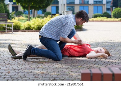 Man trying to help unconscious woman on the street