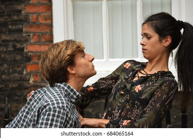 Man trying to kiss woman
