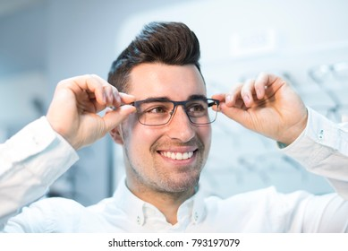 Man trying on glasses in optical store while smiling