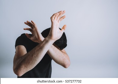 Man trying to protect himself with his arms. Terrified young guy is blocking the atack or violence and crossing arms over his head. Isolated on white background