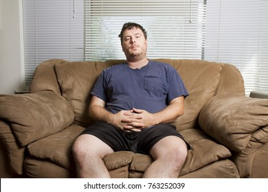 Man is trying to relax on the couch after a long day