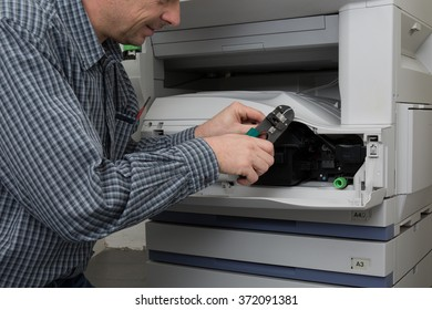 Man is trying to repair the office printer at work
