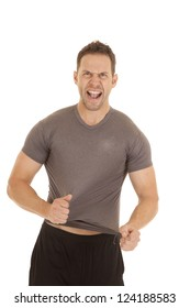 A man trying to rip off his tight fitting shirt.