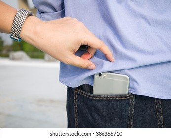 A man trying to steal a smartphone in the back pocket of blue jeans