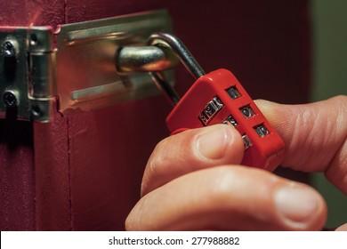man trying to unlock combination lock