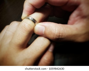 a man trying to wear a ring. unfortunately his finger is too big or the ring is too small