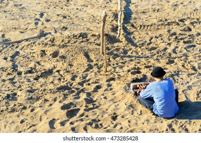 A man in a t-shirt with blue stripes and hat preparing barbecue on a sandy beach.