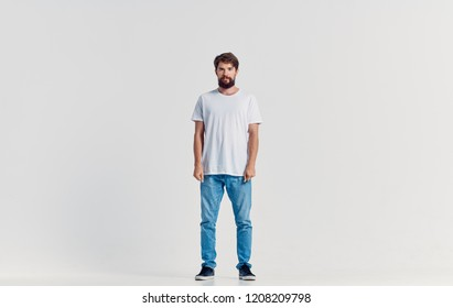 a man in a t-shirt and jeans stands on a light background