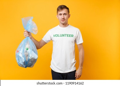 Man in t-shirt volunteer hold trash bag isolated on yellow background. Voluntary free assistance charity grace. Environmental pollution problem. Stop nature garbage environment protection concept