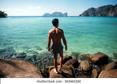 Man turned back to the camera looking at the sea, relaxed, concept of freedom. Gym handsome brunette hair man with nude torso on the beach in Phi Phi island, Thailand