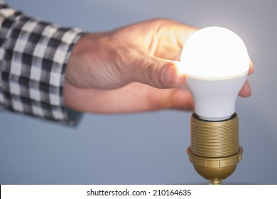 A man turning a lighted fluorescent lightbulb in his own house