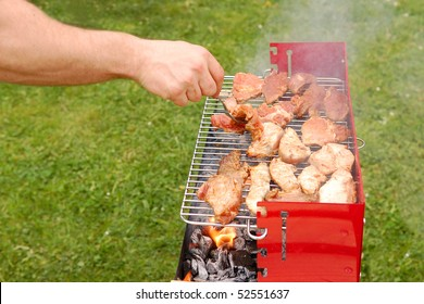 Man turning meat on a barbecue grill with green grass