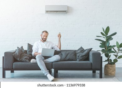 man turning on air conditioner with remote control while using laptop on sofa - Shutterstock ID 1136979338