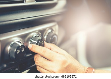 Man Turning on car air conditioning system,finger hitting car emergency light botton,Hand tuning fm radio button in car panel.