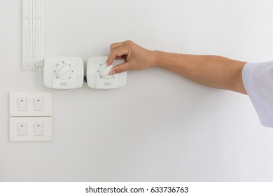 A man turning on a electric cycle fan dimmer switch.