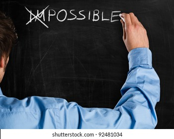 """Man turning the word """"Impossible"""" into """"Possible"""""""