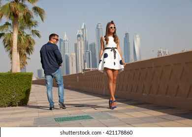 Man turns on beautiful women with long legs. UAE summer destination.