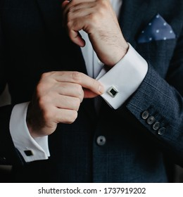 Man in a Tux fixing his Cufflink.