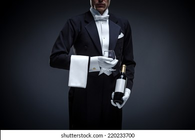 Man in a tuxedo with bottle and glass