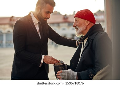 Man in tuxedo came up to beggar to help, give money donation. Rich man hold out his hand with money to homeless person. People relationship concepr