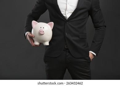 Man in tuxedo holding a pig money box