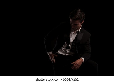 man in tuxedo is looking down to his ring on black background
