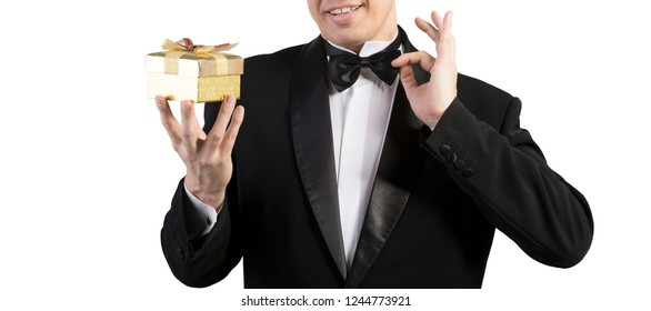man in tuxedo witch golden gift box