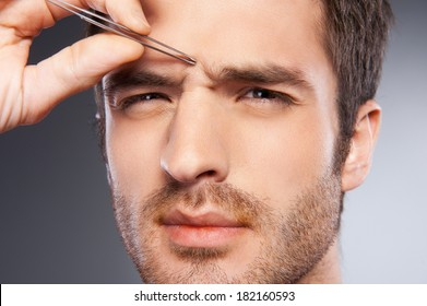 Man tweezing eyebrows. Frustrated young man tweezing his eyebrows and looking at camera while standing isolated on grey background