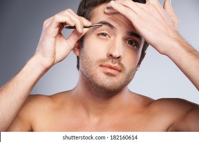 Man tweezing his eyebrows. Handsome young man tweezing his eyebrows and looking at camera while standing isolated on grey background