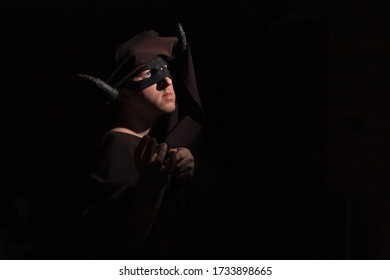 A man with twisted horns in a dark cape, mask and turban depicts a demon on a dark background with copyspace