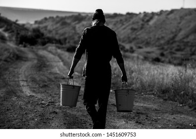 Man with two bucketful of water. A village man carrying two buckets. water crisis.