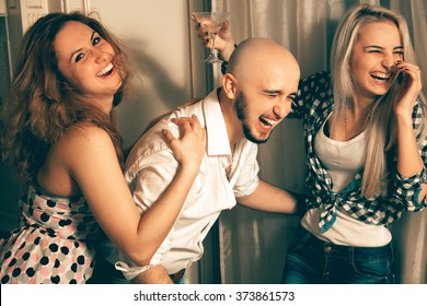 man with two charming girls laughing at a party. Celebrate, disco, party, nightlife, entertainment, friendship concept.