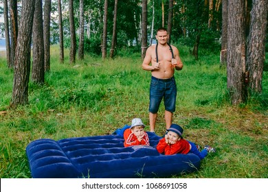 man with two children pumped up blue air mattress in the woods in the summer