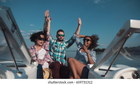Man with two girl celebrating while sailing on boat and enjoying day.