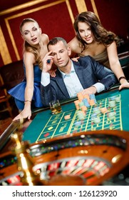 Man with two girls playing roulette at the casino club. Addiction to the gambling