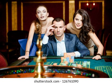Man with two ladies playing roulette at the casino. Addiction to the gambling