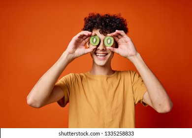 A man with two slices of kiwi in front of his eyes is smiling at the camera