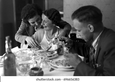 Man and two woman eating pasta in restaurant