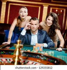 Man with two women playing roulette at the casino. Addiction to the gambling
