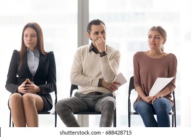 Man and two women sitting on chairs in row, expressing different emotions, worried girl, thoughtful guy, serious concentrated young lady waiting for their turn on interview, actors having audition