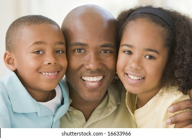 Man and two young children embracing and smiling