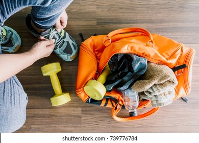 Man tying her shoelaces with bag and fitness equipment