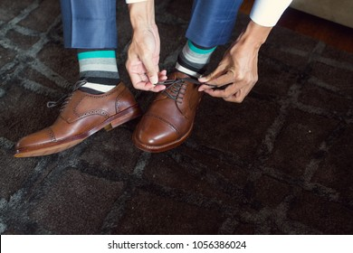 The man is tying his shoes. Striped socks.