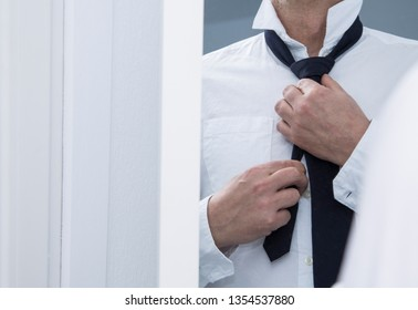 man tying his tie in front of the mirror