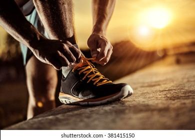 Man tying jogging shoes