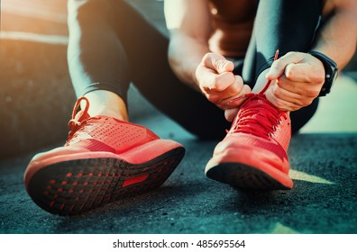 Man tying jogging shoes.He is running outdoors on a sunny day.