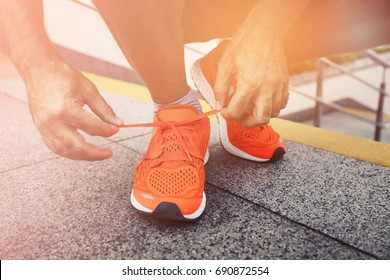 Man tying jogging shoes.A person running outdoors on city stairs. vintage color
