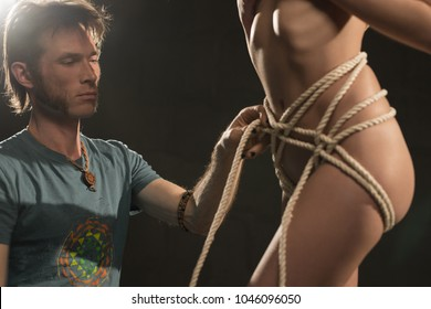 Man tying nude woman with rope cropped view