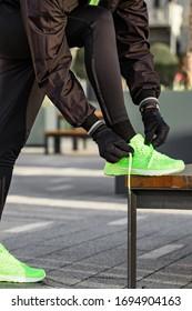 Man tying running shoes in urban park.